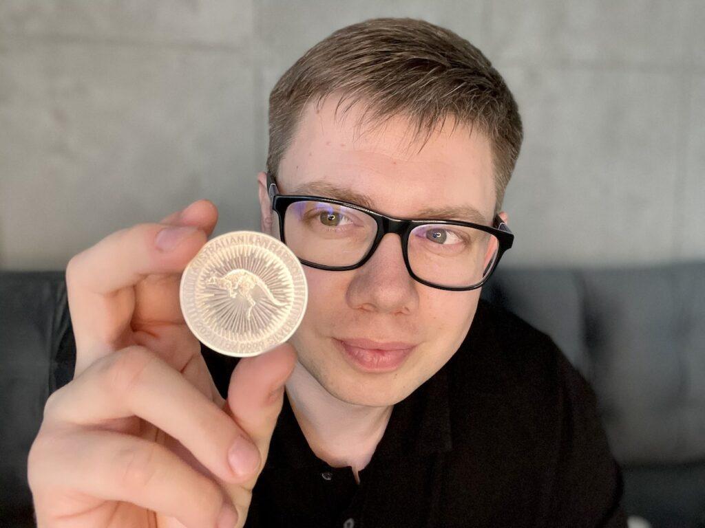 Łukasz Cichocki trzymający jednouncjową srebrną monetę Australijski Kangur